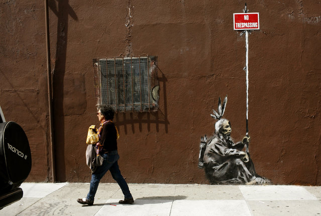 A woman walks past a drawing, believed to be the work of elusive British street artist Banksy, in the Mission District of San Francisco, May 4, 2010. (Photo by Robert Galbraith/Reuters)