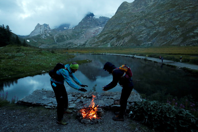 Competitors warm up by a fire at the Lake Combale during the 16th Ultra-Trail du Mont-Blanc (UTMB) race near Courmayeur, Italy on September 1, 2018. (Photo by Denis Balibouse/Reuters)