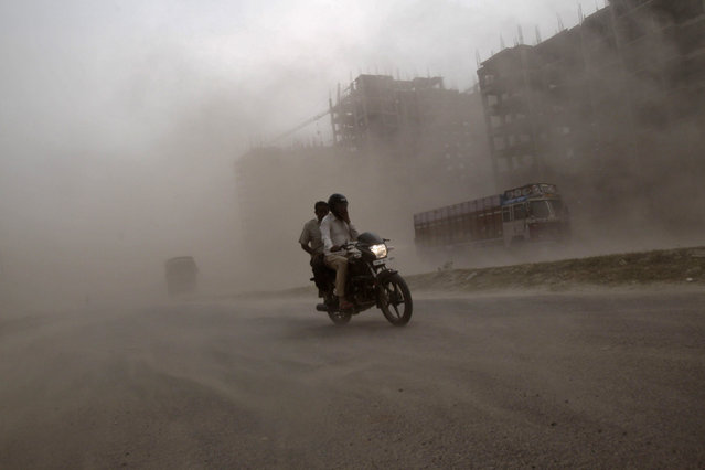 Men ride a motorcycle through a heavy dust storm along a road in Greater Noida on the outskirts of New Delhi, India October 23, 2012. (Photo by Vivek Prakash/Reuters)