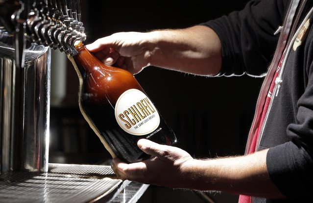 In this photo made Friday, March 27, 2015, an employee demonstrates for a photograph the pouring of a growler of beer at Schlafly Tap Room in St. Louis. A bill is moving through the Missouri Legislature that would allow the sale of jugs of beer, known as growlers, at convenience and grocery stores. (Photo by Jeff Roberson/AP Photo)