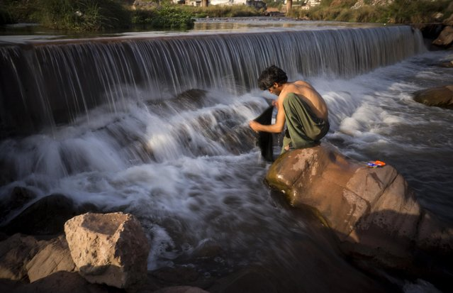 A Pakistani laborer washes clothes at a polluted stream outside Islamabad, Pakistan, Wednesday, March 25, 2015. (Photo by B. K. Bangash/AP Photo)