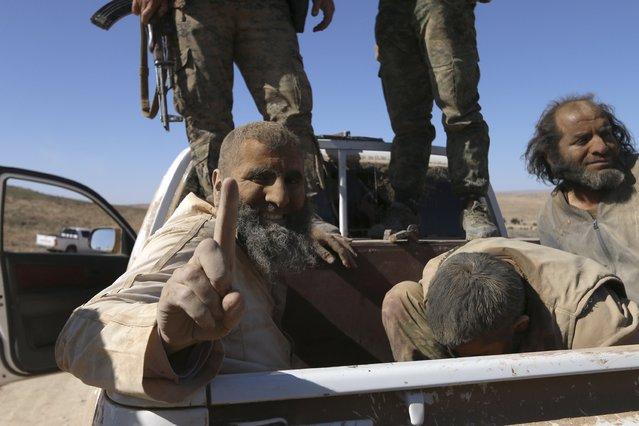 An Islamic State fighter fighter gestures while being held as prisoner with fellow fighters under Democratic Forces of Syria fighters as they ride a pick-up truck near al-Shadadi town, Hasaka countryside Syria February 18, 2016. (Photo by Rodi Said/Reuters)