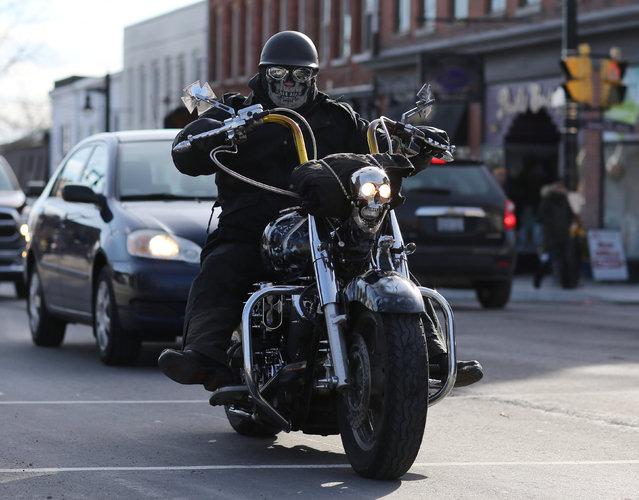 A masked biker cruises down Main Street during a below-freezing Friday the 13th motorcycle rally in Port Dover, Ontario, Canada January 13, 2017. For the event which is held in all seasons, the temperatures in Port Dover on Friday ranged from a low of minus five degrees Celcius (23 degrees Fahrenheit) to a high of minus one degree Celcius (30 degrees Fahrenheit) and with a windchill of  minus 11 degrees Celcius (12 degrees Fahrenheit). (Photo by Peter Power/Reuters)