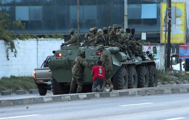 A supporter of main opposition leader Hakainde Hichilema kneels as a soldier assaults him, on a street,  in Lusaka, Zambia, Sunday August 15, 2021. Veteran Zambian opposition leader Hakainde Hichilema appears on the verge of clinching the country's presidency, with a commanding lead in votes. The 59-year old businessman, contesting the presidency for the sixth time, has more than 2.3 million votes to President Edgar Lungu's 1.4 million votes, according to results announced Sunday by the Electoral Commission of Zambia. Hichilema narrowly lost two previous elections to Lungu in 2015 and 2016. (Photo by Tsvangirayi Mukwazhi/AP Photo)