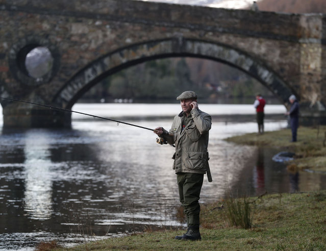 An angler speaks on his mobile phone as he fishes on the opening day of the salmon fishing season on the River Tay at Kenmore in Scotland, Britain January 16, 2017. (Photo by Russell Cheyne/Reuters)