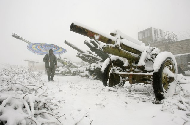 A Lebanese man holding a umbrella walks past abandoned Israeli cannons during a snow storm in the southern village of Khiam, on the Israeli-Lebanese border, on December 13, 2013. (Photo by Mahmoud Zayyat/AFP Photo)