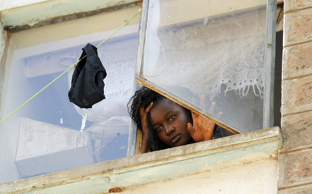 A student at the University of Nairobi looks down from the window at the Kimberly ladies hostels at the Kikuyu campus near the capital Nairobi, April 12, 2015. A Kenyan student died and more than 100 others were injured as they fled after a electricity transformer explosion before dawn on Sunday triggered fears that their campus was being attacked, officials said. (Photo by Thomas Mukoya/Reuters)