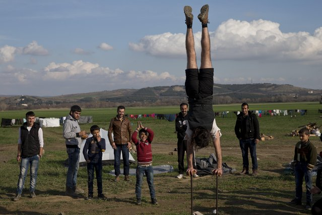 A volunteer performs to entertain refugees while waiting to be allowed to continue their trip to southern Macedonia, near the northern Greek village of Idomeni, Thursday, February 25, 2016. The Greek interior ministry said about 12,000 people have been stranded in Greece since neighbor Macedonia began turning Afghan immigrants away at the border and slowing the number of crossings for others heading to central and northern Europe. (Photo by Petros Giannakouris/AP Photo)