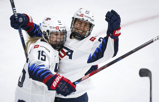 Alex Carpenter, right, of the United States, celebrates her goal with teammate Savannah Harmon during first period gold medal final IIHF Women's World Championship hockey action against Canada in Calgary, Tuesday, August 31, 2021. (Photo by Jeff McIntosh/The Canadian Press)