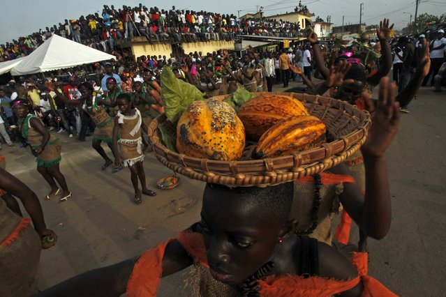A participant carrying cocoa pods takes part in a parade during the Popo (Mask) Carnival of Bonoua, in the east of Abidjan, April 18, 2015. (Photo by Luc Gnago/Reuters)