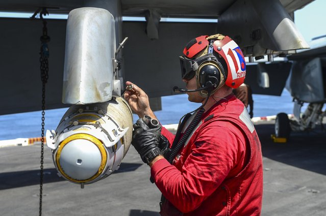 A Sailor prepares ordinance for an F/A-18F Super Hornet on the flight deck of the aircraft carrier USS Theodore Roosevelt in this U.S. Navy photo taken April 21, 2015. (Photo by Mass Communication Specialist 3rd Class Josh Petrosino/Reuters/U.S. Navy)