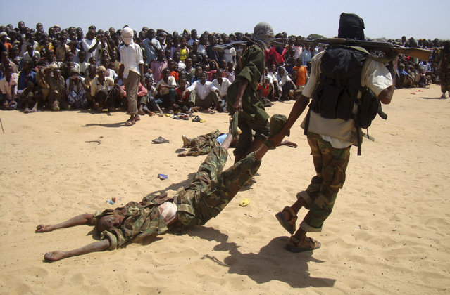 Members of al Shabaab display the body of one of seven suspected Burundian peacekeepers from the African Union Mission to Somalia (AMISOM) who were killed during clashes in Somalia's capital Mogadishu, February 24, 2011. (Photo by Feisal Omar/Reuters)