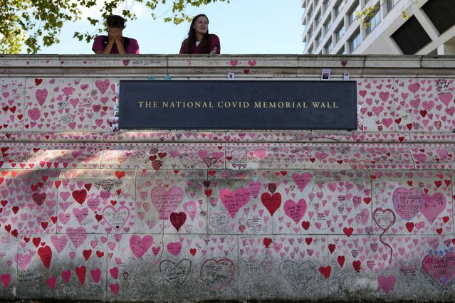 Nurses from the nearby hospital rest atop the National Covid Memory Wall in London, Thursday, September 16, 2021. Although the number of people now contracting COVID-19 is way higher than this time last year – over 30,000 new infections a day – the British government has opted not to re-introduce further virus restrictions for England, as the vaccine drive this year has reduced the number of people requiring treatment for COVID-19 and subsequently dying. (Photo by Frank Augstein/AP Photo)