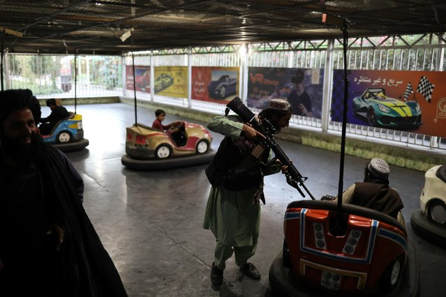 Taliban soldiers ride bumper cars at an amusement park in Kabul, Afghanistan on September 13, 2021. (Photo by WANA via Reuters)