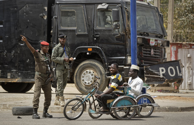 Security forces direct two disabled men in hand-pushed wheelchairs away from a road which has been closed to vehicles for security reasons, leading to the electoral commission offices in Kano, northern Nigeria Monday, February 25, 2019. Nigeria is counting votes in its presidential election and observers are giving mixed assessments of the process. (Photo by Ben Curtis/AP Photo)