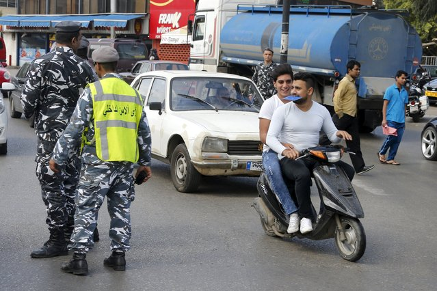 Men ride on a scooter without helmets, as one of them holds a booklet of the new traffic law, as they pass policemen controlling traffic in Beirut, April 22, 2015. A new rigid traffic law is expected to be implemented in Lebanon on April 22 with heavy penalties for drivers not following rules. Lebanon in 2014 lost 900 people to traffic incidents, according to road safety group YASA. (Photo by Mohamed Azakir/Reuters)