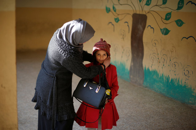 A mother adjusts her daughter's hat before she enters a classroom in school in Mosul, Iraq, January 23, 2017. (Photo by Muhammad Hamed/Reuters)
