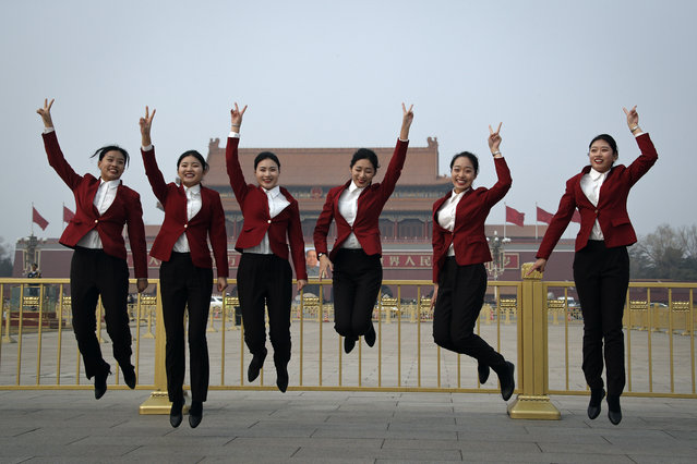 Hospitality staff jump as they pose for photographs on Tiananmen Square during the opening session of the Chinese People's Political Consultative Conference (CPPCC) held at the Great Hall of the People in Beijing, Sunday, March 3, 2019. (Photo by Andy Wong/AP Photo)