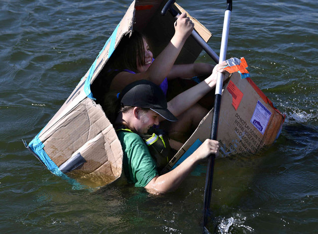 Izabella McCutchen, in green, and Hannah Collins, both 12, keep paddling as their S.S. Sharqueisha takes on water and slowly folds inward halfway through the course Saturday, September 18, 2021, in Abilene, Texas. Local Scouts held their first Cardboard Boat Regatta on Lake Fort Phantom Hill at the Abilene Sailing Association. (Photo by Ronald W. Erdrich/The Abilene Reporter-News via AP Photo)