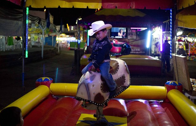 In this March 18, 2015 photo, a boy rides a mechanical bull for children at the Texcoco Fair on the outskirts of Mexico City. In Mexico, these types of fairs date back to Spanish colonial times, and in some smaller communities they are organized around the feast days of Roman Catholic saints. (Photo by Eduardo Verdugo/AP Photo)
