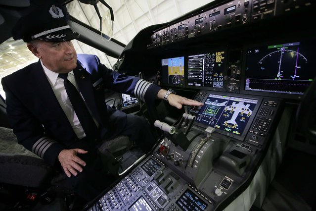 Captain Bruce Johnson explains the cockpit instruments of American Airlines' first Boeing 787 Dreamliner at the airline's maintenance hangar at Dallas-Fort Worth International Airport, Wednesday, April 29, 2015, in Grapevine, Texas. American Airlines unveiled the new passenger jet to employees and media before it goes into service May 7. (Photo by L. M. Otero/AP Photo)