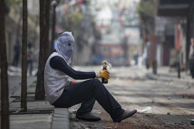 A masked protester holds a Molotov cocktail as he sits during clashes with police in Okmeydani neighbourhood in Istanbul, Turkey, May 1, 2015. (Photo by Kemal Aslan/Reuters)