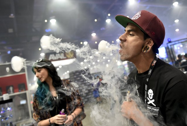 Angel Huezo, right, creates jellyfish-like figurines as he exhales at the Vape Summit 3 in Las Vegas, Nevada May 2, 2015. (Photo by David Becker/Reuters)