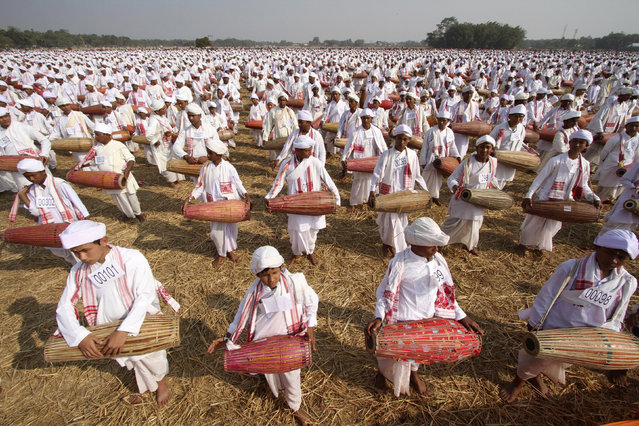 People in traditional attires play their drums during an attempt to enter the Guinness Book of World Record at a field in Titabar town in the northeastern Indian state of Assam January 6, 2013. A total of 14,833 Assamese people attempted to enter the Guinness Book of World Record by playing the drums for 15 minutes non stop, organizers said. (Photo by Utpal Baruah/Reuters)