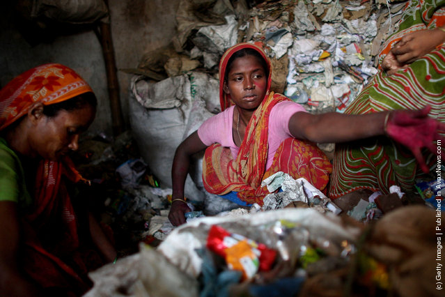 Women work for a recycling business by sorting through trash for usable paper products in Dhaka, Bangladesh