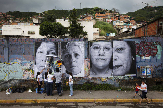 "Volunteers put up large portraits of women whose children were victims of violence, in Caracas, Venezuela November 19, 2011. Close to 52 five-metre high portraits were pasted on walls of poor and commercial areas of the city as part of a project called ""Esperanza"" (hope) by JR. The project is in line with JR's project ""Inside Out"", which aims to highlight stories about ordinary people through large portraits displayed on outdoor facades. (Photo by Carlos Garcia Rawlins/Reuters)"