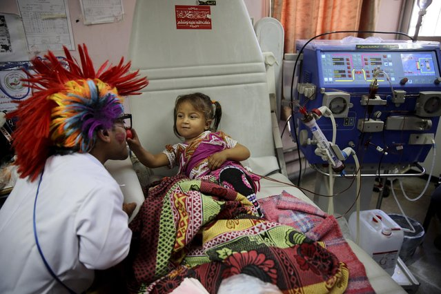 In this Thursday, March 17, 2016 photo, 33-year-old Palestinian clown doctor Alaa Miqdad, left, entertains 3-year-old patient Yaqin Shawaf, who suffers from dialysis, in the department of kidney diseases at Al-Rantisi children's hospital in Gaza City. (Photo by Adel Hana/AP Photo)