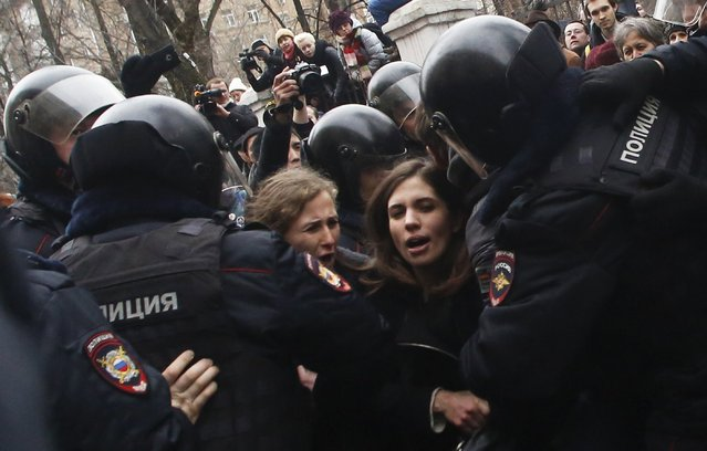 Russian police officers detain members of the p*ssy Riot punk group, Nadezhda Tolokonnikova, center right, and Maria Alekhina, center left, outside a court room in Moscow, Russia, Monday, February 24, 2014, where hearings started against opposition activists detained on May 6, 2012 during a rally at Bolotnaya Square. (Photo by Denis Tyrin/AP Photo)