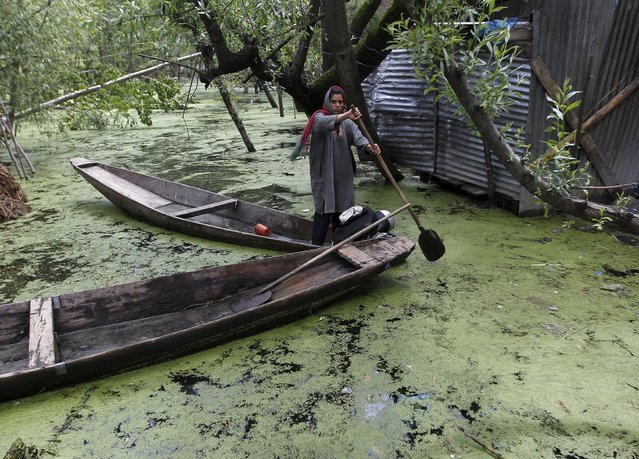 A woman paddles her boat in her water-logged courtyard after recent rains in the interiors of Dal Lake in Srinagar April 28, 2015. (Photo by Danish Ismail/Reuters)