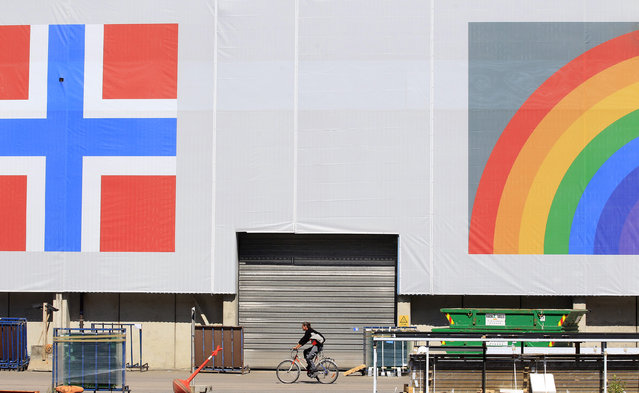 4. NORWAY: A man cycles past a banner featuring the Norwegian flag and a rainbow hanging on a warehouse in Oslo, Norway June 20, 2012. (Photo by Cathal McNaughton/Reuters)