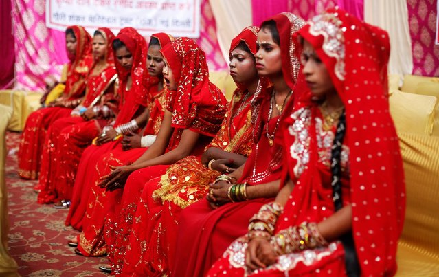 An Indian bride yawns as she waits with others for the rituals to begin before a mass community marriage in New Delhi, India, Thursday, February 27, 2014. Thirteen couples were married in a mass marriage organized by Gauri Shankar charitable trust. (Photo by Altaf Qadri/AP Photo)