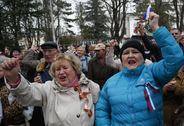 Pro-Russia demonstrators rally in front of the local parliament building in Crimea's capital Simferopol, Ukraine, Thursday, March 6, 2014. About 50 people rallied outside the local parliament Thursday morning waving Russian and Crimean flags. Lawmakers in Crimea called a March 16 referendum on whether to break away from Ukraine and join Russia instead, voting unanimously Thursday to declare their preference for doing so. (Photo by Sergei Grits/AP Photo)