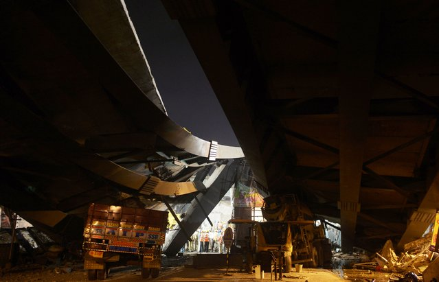Vehicles are parked under the wreckage of a collapsed flyover as rescue efforts continue in the Indian city of Kolkata on March 31, 2016. Hundreds of emergency workers in India battled March 31 to rescue dozens of people still trapped after a flyover collapsed onto a busy street, killing at least 20 people and injuring nearly 100. (Photo by Dibyangshu Sarkar/AFP Photo)