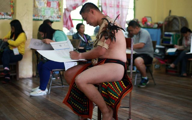 """A member of the Filipino indigenous tribe """"Igorot"""" clad in traditional costume casts his election ballot at a school used as a polling station in Baguio City, Mountain Province, northern Philippines, 13 May 2019. Over 61 million Filipinos are expected to cast their vote in the country's mid-term elections, wherein over 43,000 candidates are vying for some 18,000 electoral posts including seats in the Philippine Senate and House of Representatives. (Photo by Darryl Go/EPA/EFE/Rex Features/Shutterstock)"""