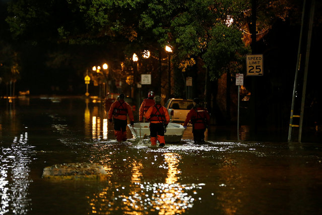 Rescue crews wade in a flooded neighbourhood after heavy rains overflowed nearby Coyote Creek in San Jose, California, U.S. February 21, 2017. (Photo by Stephen Lam/Reuters)