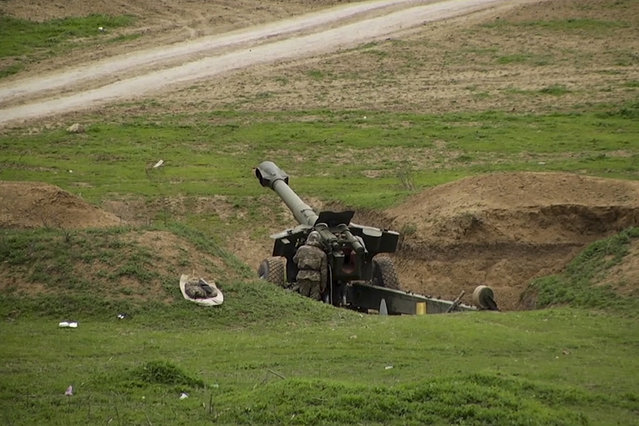 In this grab taken from Associated Press Television footage made available on Monday, April  4, 2016, Armenian soldiers aim a howitzer on Sunday, April 3, 2016, in the village of Mardakert, in the separatist region of Nagorno-Karabakh. (Photo by Associated Press Television via AP Photo)