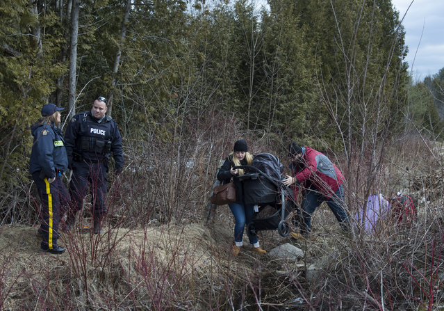 A couple who claimed to be from Turkey struggles to get their baby and baby carriage across the US/Canada border February 27, 2017, in Champlain, New York. There continues to be an increasing number of people crossing the US border into Canada illegally. (Photo by Don Emmert/AFP Photo)