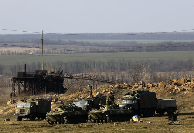 Ukrainian soldiers are seen atop armoured vehicles at a Ukrainian Army military camp set up on a field close to the Russian border in east Ukraine March 24, 2014. (Photo by Yannis Behrakis/Reuters)