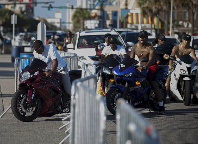 Bikers ignore a fenced boundary after having engine problems from a overheated motorcycle on Ocean Boulevard during the 2015 Atlantic Beach Memorial Day BikeFest in Myrtle Beach, South Carolina May 24, 2015. (Photo by Randall Hill/Reuters)
