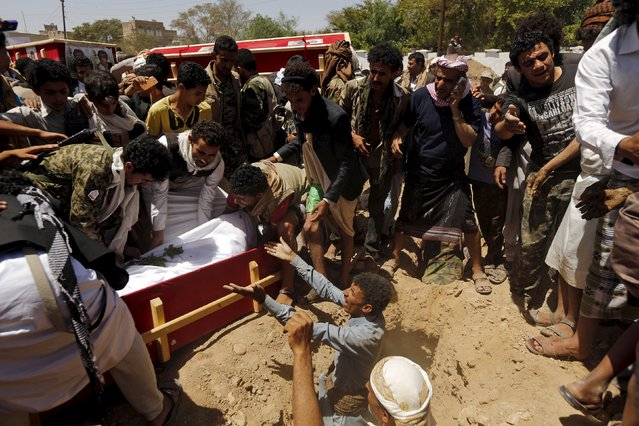 Houthi followers lower the body of a Houthi fighter in a coffin as they bury him in Sanaa May 15, 2015. (Photo by Khaled Abdullah/Reuters)