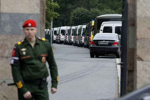 Buses carrying bodies of the 14 crew members who died in a fire on a Russian navy's deep-sea research submersible, drive to the Serafimovskoye memorial cemetery during a funeral ceremony in St. Petersburg, Russia, Saturday, July 6, 2019. Russian President Vladimir Putin has awarded the nation's highest honors to 14 seamen who died in a fire on one of the navy's research submersibles. (Photo by Dmitri Lovetsky/AP Photo)