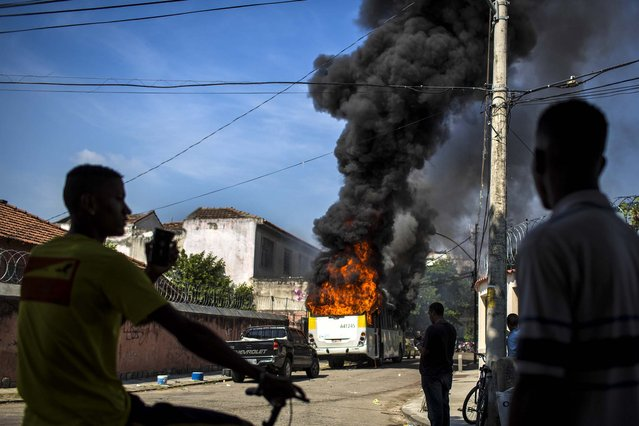 People watch a bus burn after it was set on fire near the area recently occupied by squatters in Rio de Janeiro, Brazil, on April 11, 2014. Squatters in city are clashing with police after a Brazilian court ordered that 5,000 people be evicted from abandoned buildings of a telecommunications company. Officers have used tear gas and stun grenades to try to disperse the families. (Photo by Felipe Dana/Associated Press)