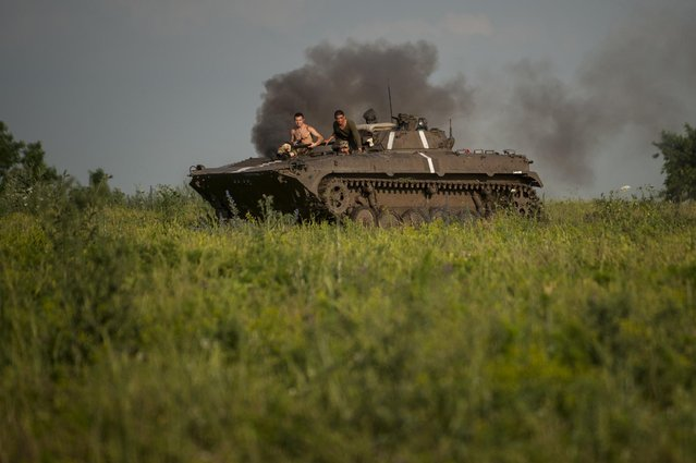 In this photo taken Monday, June 22, 2015, Ukrainian servicemen ride atop an armored vehicle at a frontline in the village of Krymske, east Ukraine. (Photo by Evgeniy Maloletka/AP Photo)