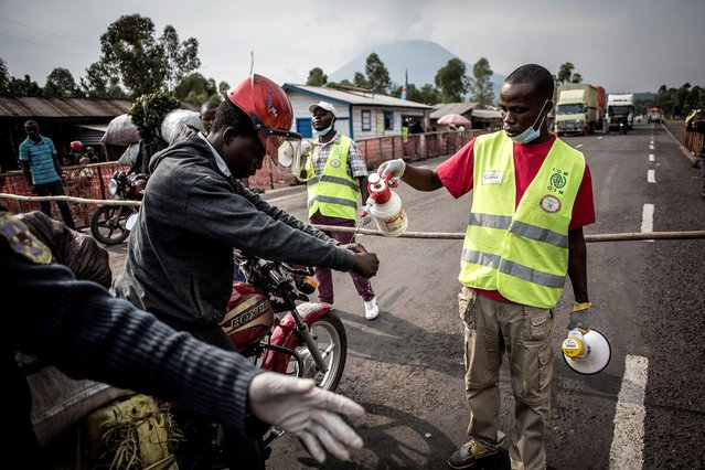 A motor taxi driver gets his hands washed at an Ebola screening station on the road between Butembo and Goma on July 16, 2019 in Goma. The first patient to be diagnosed with Ebola in the eastern DR Congo city of Goma has died, the governor of North Kivu province said on July 16, 2019. The case – the first in a major urban hub in the region's nearly year-old epidemic of the disease – has sparked deep concern in neighbouring Rwanda and at the UN. (Photo by John Wessels/AFP Photo)