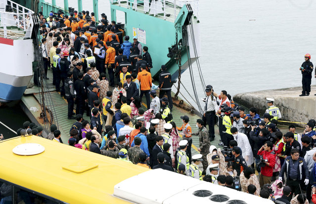 Rescued passengers are escorted by members of a rescue team upon their arrival at a port in Jindo, south of Seoul, South Korea, Wednesday, April 16, 2014. (Photo by Park Chul-heung/Reuters/Yonhap)