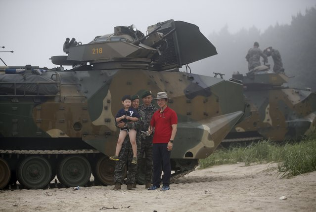 A tourist takes a selfie with his son and South Korean Marines in front of amphibious assault vehicles of the South Korean Marine Corps during a landing operation drill in Taean, South Korea, June 29, 2015. (Photo by Kim Hong-Ji/Reuters)